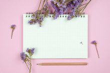 Top View Of Blank Notebook And Flower On Pink Background