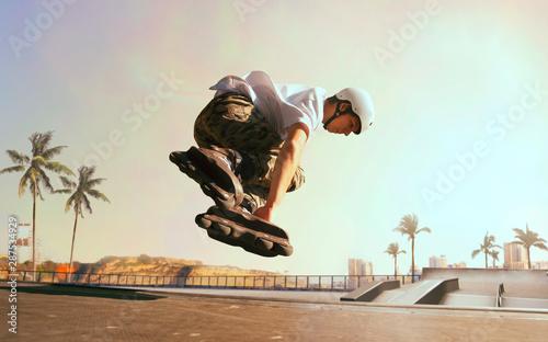 Fotografia Rollerskater man is performing tricks in skatepark on sunset.