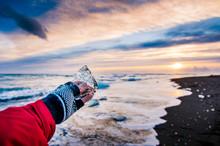 Traveler Holding Ice Chunk On Diamond Beach In Iceland