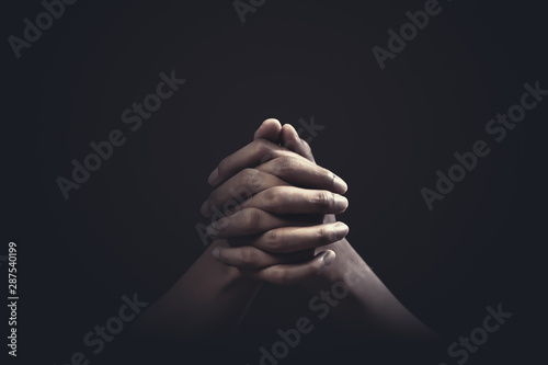 Leinwand Poster  Praying hands with faith in religion and belief in God on dark background