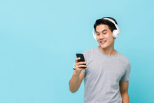 Asian Man Wearing Headphones Listening To Music From Smartphone
