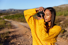 Young Woman On A Rural Trail Taking Photos