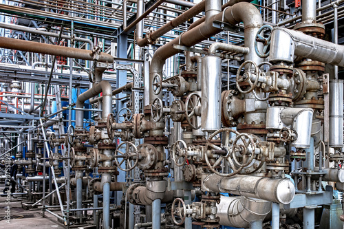 фотография Oil and gas industrial refinery zone,Detail of equipment oil pipeline steel with valve from large oil storage tank at cloudy sky