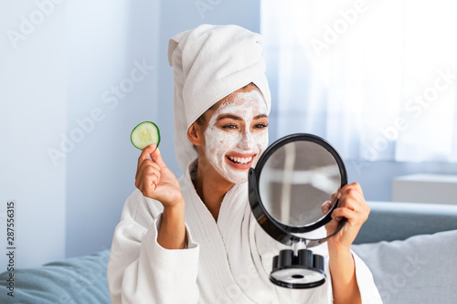Woman with facial mask and cucumber slices in her hands Fototapeta