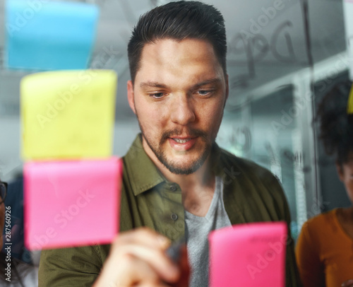Fototapety, obrazy: Portrait of a businessman brainstorming new startup business and writing on sticky notes stuck on transparent glass in office