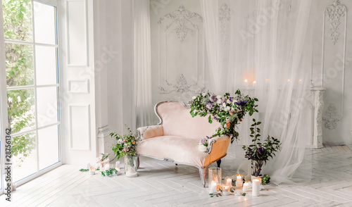 vintage sofa of soft pink color, decorated with flowers and greens, stands in a classic room on a white wooden floor surrounded by lighted candles in glass candlesticks near  large window and curtains