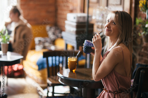 beautiful pensive calm relaxed girl blonde sits at a table in a retro vintage st Wallpaper Mural