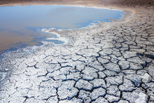 Heat, Drought, Disaster, Saline Soil, Dry Riverbed, Blue Sky Reflected In The Remnants Of Water. Bright, Beautiful Natural Landscape. Close-up, Background, Wallpaper, Design. Selective Focus.