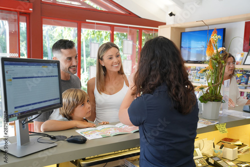 Fotografering Family checking-in at hotel reception desk