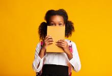 Black Schoolgirl Hiding Behind Book Over Yellow Background