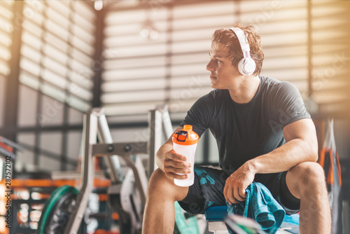 Portait of athletic man in headphones looking aside while listening to music and holding a towel and a classic fitness shaker with pre-workout drink in it. Horizontal shot