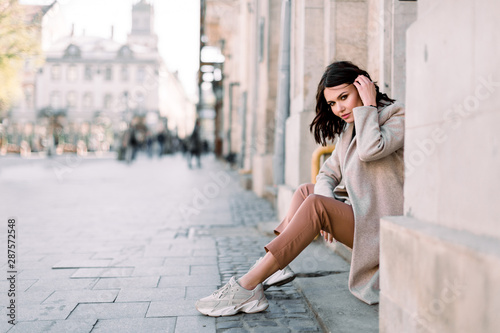 obraz dibond Outdoor portrait of a young beautiful fashionable lady sitting on stairs of old building on a street of the old city. Model wearing stylish clothes. Female fashion concept. City lifestyle.