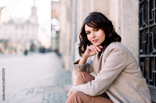 Canvastavla  Portrait of young beautiful lady in brown pants and beige coat sitting on the stone stairs near the old building in city