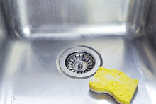Cleaning Polished Stainless Shiny Sink With Scrub Sponge