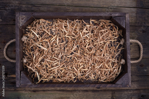Photo Wooden box with shavings straw filling on table