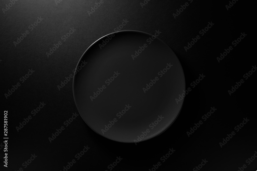 Fototapety, obrazy: Empty round black plate on dark moody black background with copy space. Overhead view