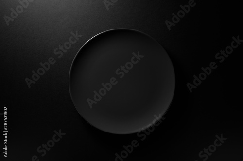 Empty round black plate on dark moody black background with copy space. Overhead view - 287581902