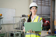 Female Industrial Engineer in the Hard Hat Uses Laptop Computer while Standing in the Industry Factory. In the Background Various Metal work Project Parts Lying.