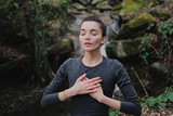 Fototapeta Zwierzęta - Young woman practicing breathing yoga pranayama outdoors in moss forest on background of waterfall. Unity with nature concept.