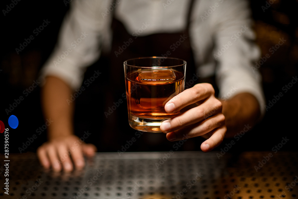 Fototapeta Professional bartender serving a cocktail in the glass with one big ice cube