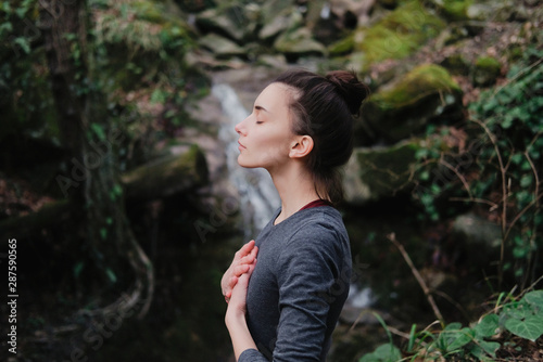 Young woman practicing breathing yoga pranayama outdoors in moss forest on background of waterfall Wallpaper Mural