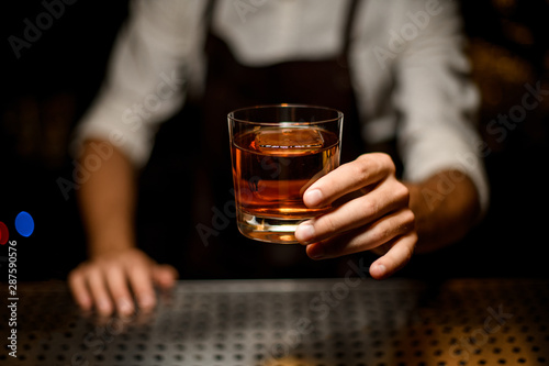 Professional bartender serving a cocktail in the glass with one big ice cube