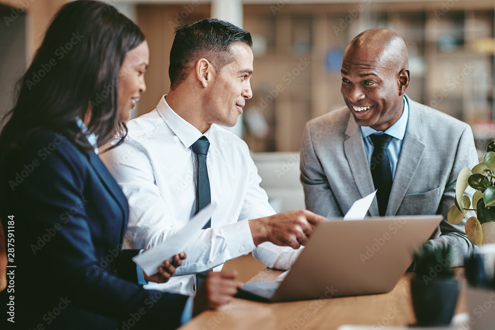 Fototapeta Smiling diverse businesspeople working together in a modern offi