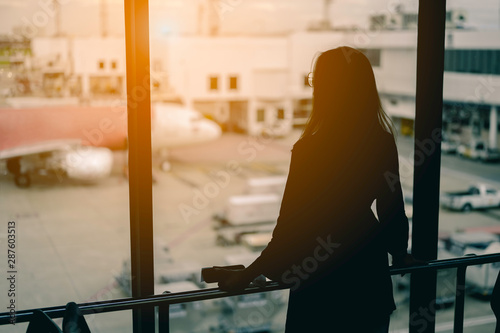 Fototapety, obrazy: Travel woman standing watching sunset at airport window.