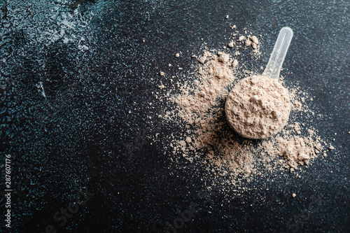 Fotografia Top view whey protein scoop on dark background, copy space