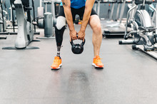Disabled Athlete With Leg Prosthesis Training At The Gym. Paralympic Sport Concept.