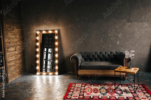 Corner room with a wooden and  gray cement wall, an aged floor, black glass doors and electric dressing makeup mirror, lights bulbs tern on, sofa Tapéta, Fotótapéta