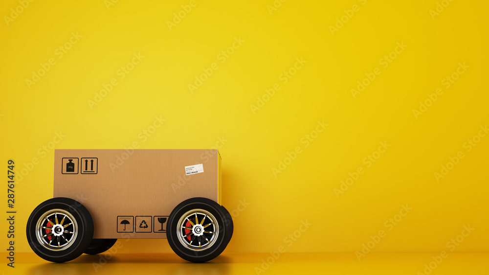 Fototapety, obrazy: Cardboard box with racing wheels like a car on a yellow background. Fast shipping by road