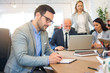 Handsome young business man writing notes on a clipboard in office