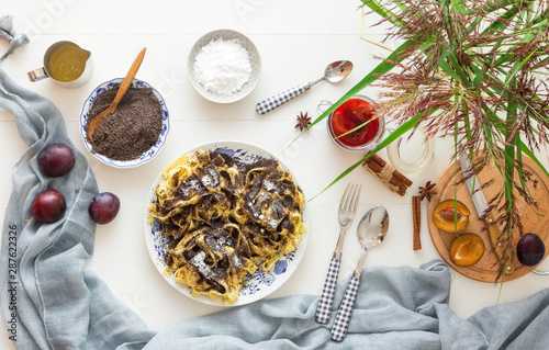 Sweet pasta dessert, noodles with poppy seeds, plum compote from fresh plums, dark background, white wooden table decorated with fresh flowers Canvas-taulu