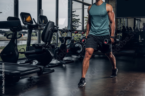 Young sportive man is doing exercises with dumbbells in empty gym club Fototapeta