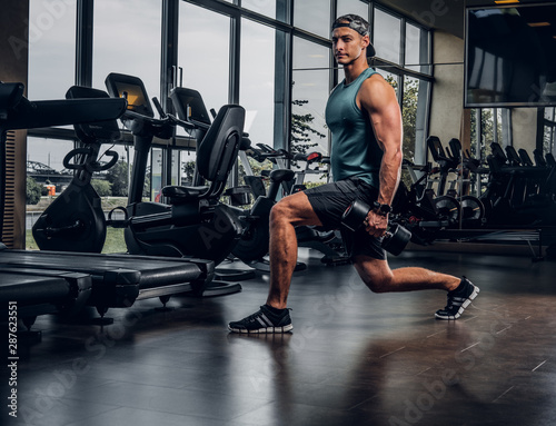 Canvas Print Young sportive man is doing exercises with dumbbells in empty gym club