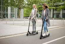 Young Women Riding Electric Scooters In The Street