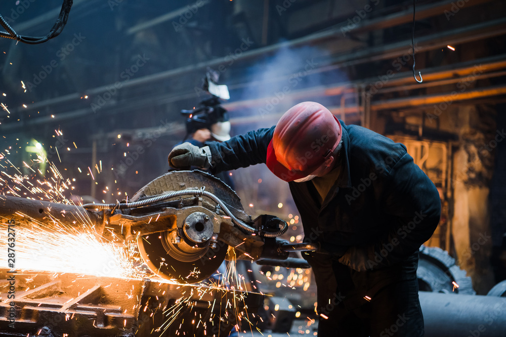 Fototapety, obrazy: Industrial worker cutting and welding metal with many sharp sparks