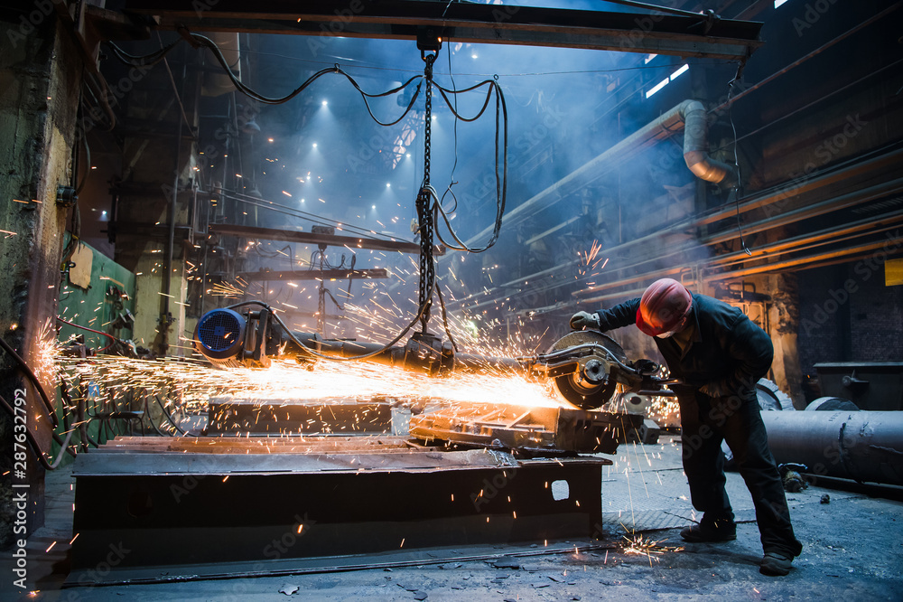 Fototapety, obrazy: Employee grinding steel with sparks - focus on grinder. Steel factory.