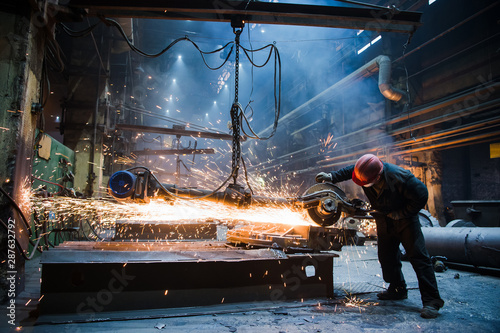 Photo Employee grinding steel with sparks - focus on grinder