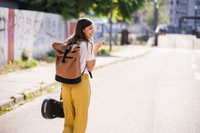 Young Woman Carrying Violin Case Using Cell Phone On The Street
