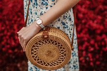 Street Style, Fashion, Trendy Summer Woman`s Outfit, Details Concept: Brown Wicker Rattan  Round Shoulder Bag, White Elegant Wrist Watch On Hand With Reptile Textured Leather Strap, Floral Print Dress