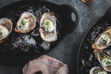 Raw Oyster With Mignonette Sauce, Celery & Cream In Cast Iron On Ice