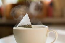 Hand Putting A Pyramid Tea Bag...
