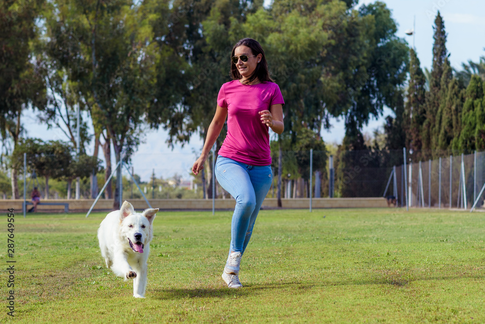 Fototapety, obrazy: Sporty woman and dog running together in the park on summer sunset. Cheerful female athlete training and exercising outdoor with her pet.
