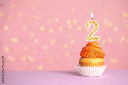 Birthday cupcake with number two candle on table against festive lights, space for text