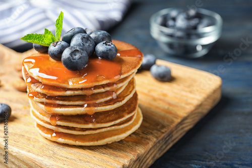 Fotografía  Wooden board with pancakes, syrup and blueberries on table, closeup