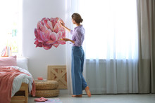 Young Interior Designer Painting Flower On Wall In Modern Room
