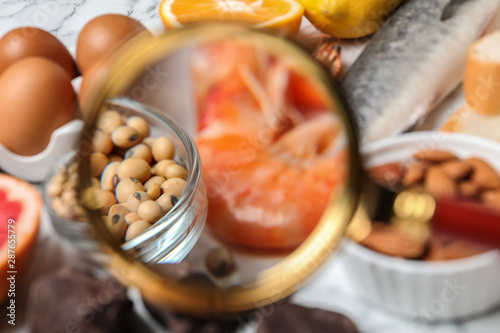 Photo Different products with magnifier focused on shrimps and soy beans, closeup