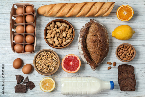 Flat lay composition of different products on white wooden table. Food allergy concept